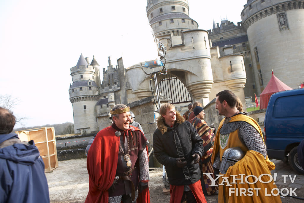 """During a break in the filming of season 2, Anthony Head and Bradley James share a lighthearted moment with another cast member.  The castle that """"plays"""" Camelot is a real location, the Chateau Pierrefonds in France, which as a public landmark could not shut down for filming - crews and actors often worked around visiting tourists."""