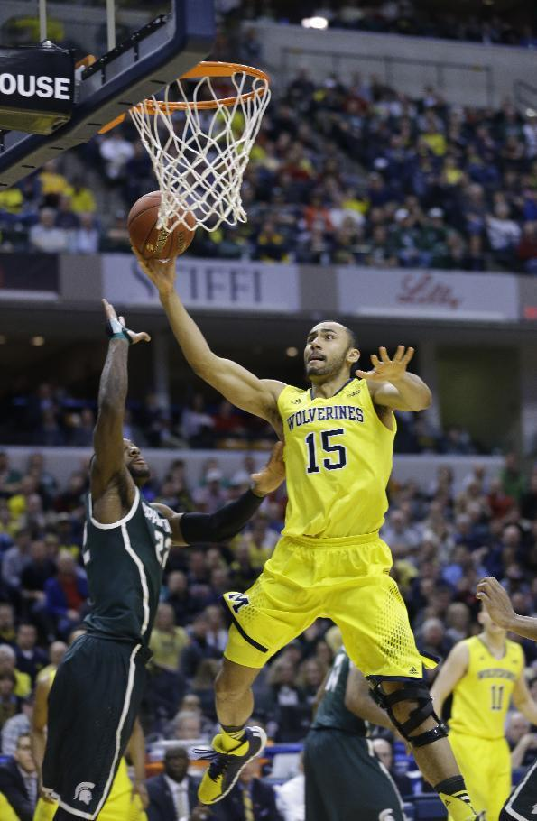 Michigan forward Jon Horford takes a shot against Michigan State guard/forward Branden Dawson in the second half of an NCAA college basketball game in the championship of the Big Ten Conference tournament Sunday, March 16, 2014, in Indianapolis. (AP Photo/Michael Conroy)