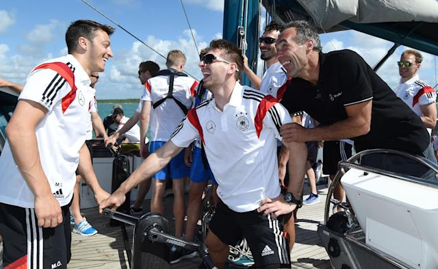German national soccer players Mesut Ozil, left, and goalkeeper Ron-Robert Zieler laugh besides explorer and adventurer Mike Horn on a boat in Santo Andre near Porto Seguro, Brazil, Tuesday, June 10, 2014. The German team got some motivation help from explorer and adventurer Mike Horn during a sailing outing near their camp on Brazil's Atlantic coast. (AP Photo/Markus Gilliar, pool)
