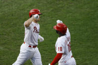 Philadelphia Phillies' J.T. Realmuto, left, and Didi Gregorius celebrate after Realmuto's home run off Atlanta Braves starting pitcher Kyle Wright during the fourth inning of a baseball game, Saturday, Aug. 8, 2020, in Philadelphia. (AP Photo/Matt Slocum)