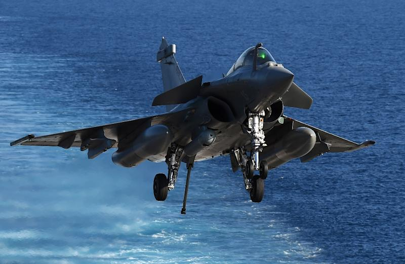 A Rafale warplane lands on the Charles-de-Gaulle aircraft carrier, deployed in the Mediterranean Sea to participate in bombing missions against Islamic State forces in Syria (AFP Photo/Anne-Christine Poujoulat)