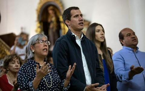 Opposition National Assembly President Juan Guaido, who declared himself interim president of Venezuela, prays next to his wife Fabiana Rosales - Credit: AP