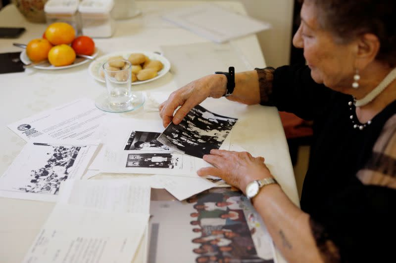 Holocaust survivor Artemis Miron, 91, sorts family photographs during an interview with Reuters in Kfar Saba, Israel
