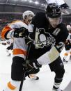 In this photo taken with a fisheye lens, Pittsburgh Penguins' Evgeni Malkin (71) is checked into the boards by Philadelphia Flyers' Braydon Coburn (5) during the second period of Game 2 of an opening-round NHL hockey playoff series in Pittsburgh, Friday, April 13, 2012. (AP Photo/Gene J. Puskar)