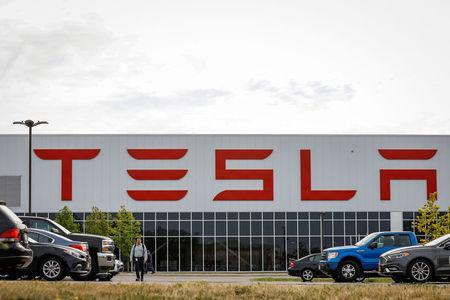 FILE PHOTO: A worker is seen outside the Tesla Inc. Gigafactory 2, which is also known as RiverBend, a joint venture with Panasonic to produce solar panels and roof tiles in Buffalo, New York