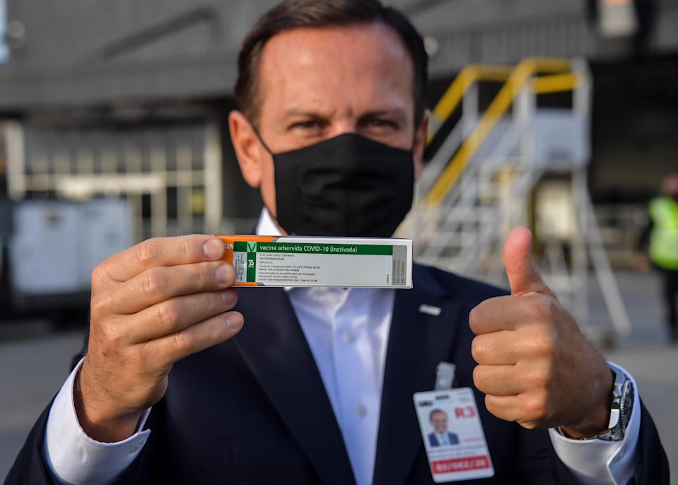 Sao Paulo Governor Joao Doria shows to members of the media a package of the CoronaVac vaccine as containers carrying doses of it are unloaded from a cargo plane that arrived from China at Guarulhos International Airport in Guarulhos, near Sao Paulo, Brazil, on December 03, 2020. - Brazil received this Thursday the second lot with 600 liters of the CoronaVac vaccine, developed by the Chinese laboratory Sinovac Biotech. (Photo by NELSON ALMEIDA / AFP) (Photo by NELSON ALMEIDA/AFP via Getty Images)