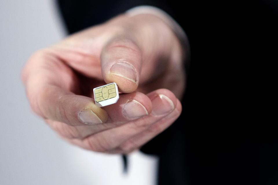 Gemalto CEO Olivier Piou shows a cell phone sim card before a press conference on February 25, 2015 in Paris. European SIM maker Gemalto said it had suffered hacking attacks that may have been conducted by US and British intelligence agencies but denied any
