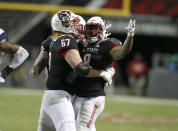 North Carolina State offensive tackle Justin Witt (67) celebrates with running back Ricky Person Jr. (8) after Person ran for a first down during the second half against Georgia Tech in an NCAA college football game in Raleigh, N.C., Saturday, Dec. 5, 2020. (Ethan Hyman/The News & Observer via AP, Pool)