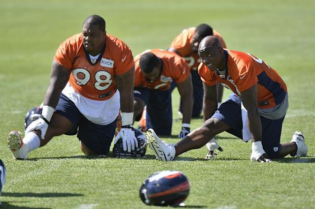 Denver Broncos' Terrance Knighton (98) and DeMarcus Ware, right, talk during stretching at an NFL football organized team activity, Monday, June 2, 2014, in Englewood, Colo. (AP Photo/Jack Dempsey)