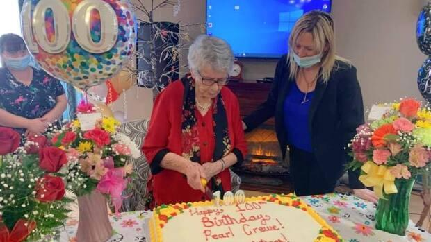 Crewe and Pleasantview Manor owner Rhonda Simms look over the cake at Crewe's 100th birthday party.