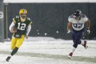 Green Bay Packers' Aaron Rodgers runs past Tennessee Titans' Matt Dickerson during the first half of an NFL football game Sunday, Dec. 27, 2020, in Green Bay, Wis. (AP Photo/Matt Ludtke)