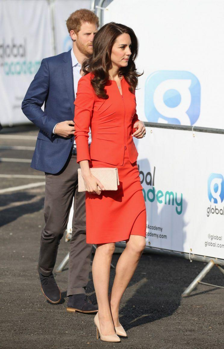 <p>Kate donned a tomato red skirt suit for the opening of The Global Academy. Her workwear look was by Armani Collezioni - the lower-priced line from the Italian brand - and featured a ruched jacket and tight-fitting pencil skirt. As always, the Duchess chose her trusty nude accessories, wearing Rupert Sanderson heels and a clutch by Etui.</p><p><i>[Photo: Getty]</i></p>