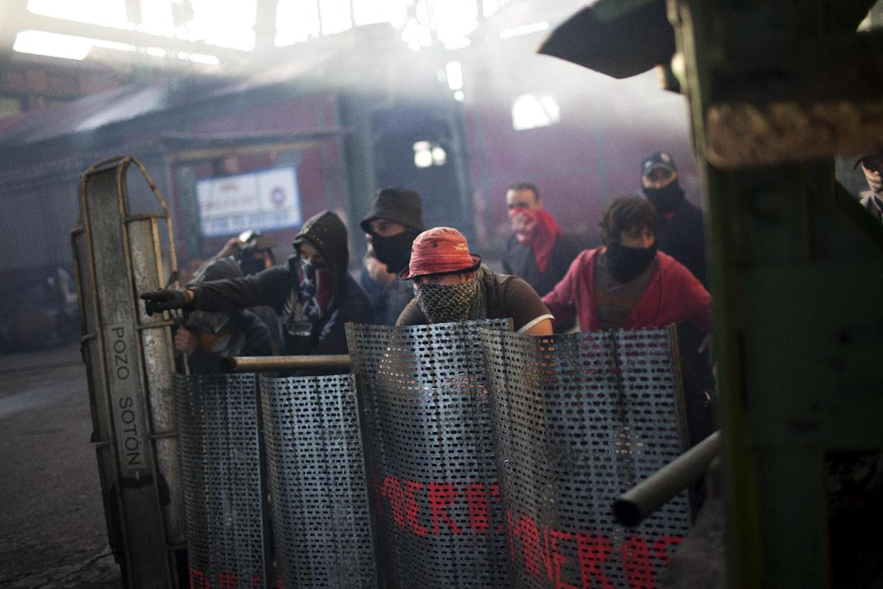 """Coal miners are seen behind their shields as they defend their position from riot police officers near the mine """"El Soton"""" during clashes in El Entrego near Oviedo, Spain, Friday, June 15, 2012. Strikes, road blockades, and mine sit-ins continue as 8,000 mineworkers at over 40 coal mines in northern Spain continue their protests against government action to cut coal subsidies. (AP Photo/Emilio Morenatti)"""