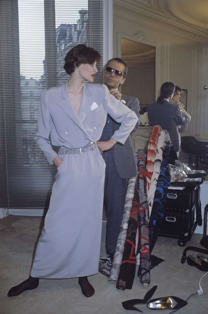 <p>Lagerfeld joined Chloé in 1964 while continuing to design for Chanel. Here, he is photographed dressing model-turned-muse Inès de La Fressange. <em>[Photo: Getty]</em> </p>