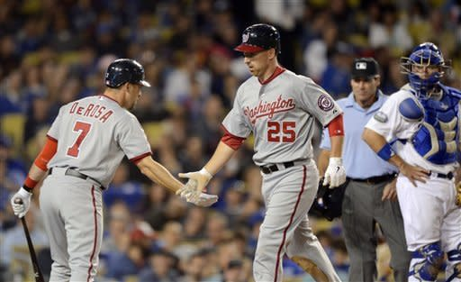 Washington Nationals' Adam LaRoche, center, is congratulated by Mark DeRosa, left, after hitting a two-run home run as Los Angeles Dodgers catcher A.J. Ellis looks on during the sixth inning of their baseball game, Friday, April 27, 2012, in Los Angeles. (AP Photo/Mark J. Terrill)