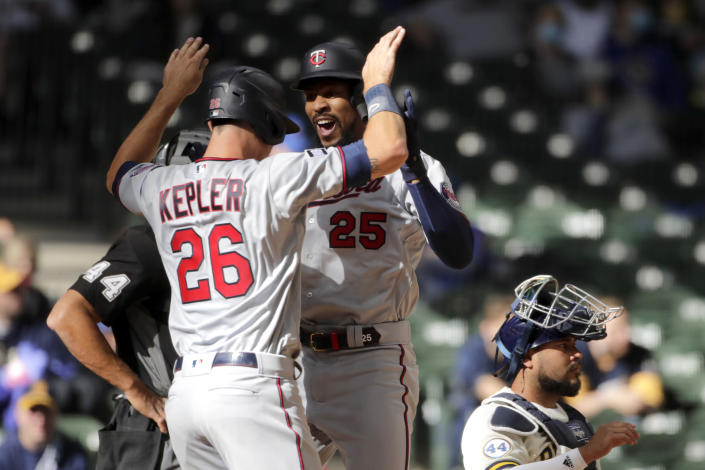 Minnesota Twins' Byron Buxton (25) is congratulated by Max Kepler (26) after hitting a two-run home run during the seventh inning of an opening day baseball game against the Milwaukee Brewers, Thursday, April 1, 2021, in Milwaukee. (AP Photo/Aaron Gash)