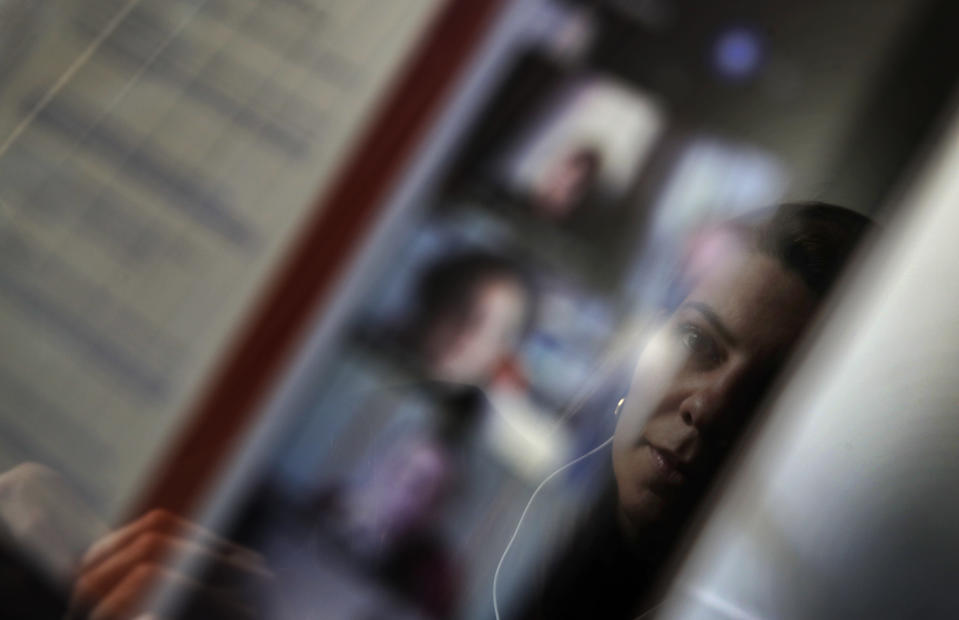 Lina Maria Fajardo of Colombia, student in psychiatry of old people is reflected in the screen of her computer as she attends a remote course in her student housing in Ivry sur Seine, outside Paris, Thursday, Feb. 11, 2021. Nearly a quarter of French young people can't find work, and many university students now rely on food aid. A hotline devoted to students has seen a surge in calls, and young people have streamed into psychiatric wards. (AP Photo/Christophe Ena)