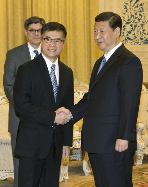 China's President Xi Jinping, right, shakes hand with U.S. Ambassador to China Gary Locke as U.S. Treasury Secretary Jacob Lew watches from behind, during their meeting at the Great Hall of the People in Beijing Tuesday, March 19, 2013. (AP Photo/Andy Wong, Pool)
