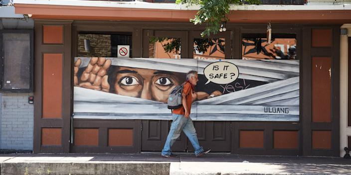 A man walking past a mural on the doors of what would normally be a bustling bar on 6th Street in Austin, Texas, on May 1.