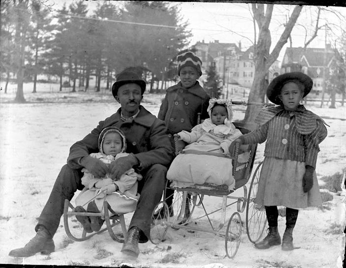 A man sits on a sled with one of his children, while another is in a baby carriage and two stand.