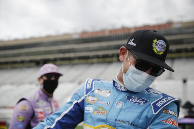 Kyle Busch, left, and Clint Bowyer, right, laugh on pit row before a NASCAR Cup Series auto race at Atlanta Motor Speedway on Sunday, June 7, 2020, in Hampton, Ga. (AP Photo/Brynn Anderson)