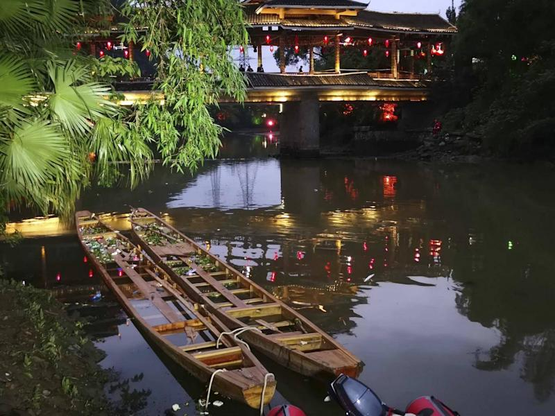 Two dragon boats that capsized, killing seventeen people, sit in the water on the Taohua River in Guilin in southern China (Chinatopix via AP)