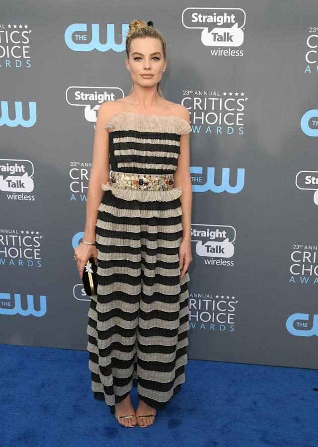 <p>The <em>I, Tonya </em>actress accessorized her striped Chanel dress with a gem belt and black bow in her hair. (Photo: Getty Images) </p>