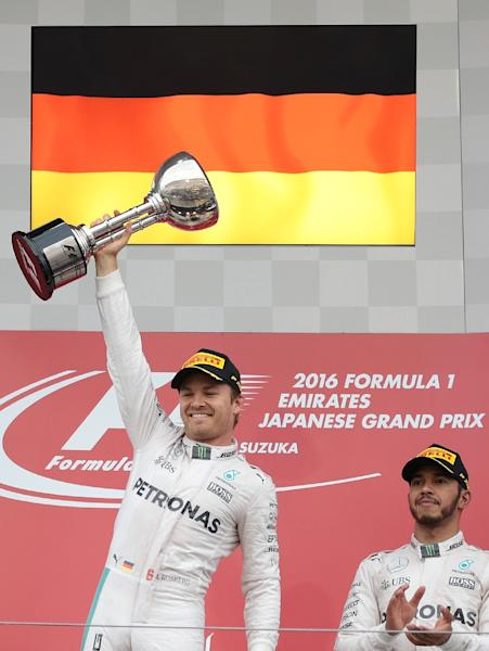 Mercedes AMG Petronas F1 Team's German driver Nico Rosberg (L) celebrates his victory on the podium next to his teammate and third-placed Mercedes AMG Petronas F1 Team's British driver Lewis Hamilton after the Formula One Japanese Grand Prix (AFP Photo/Yuya Shino)