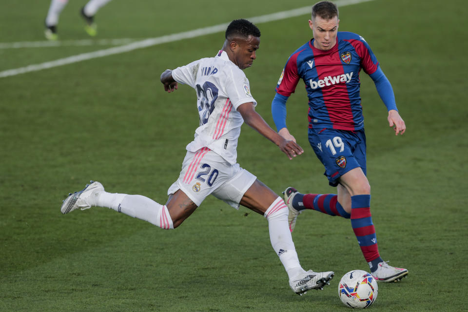 Real Madrid's Vinicius Junior, left, runs with the ball next to Levante's Carlos Clerc during the Spanish La Liga soccer match between Real Madrid and Levante at the Alfredo Di Stefano stadium in Madrid, Spain, Saturday, Jan. 30, 2021. (AP Photo/Manu Fernandez)