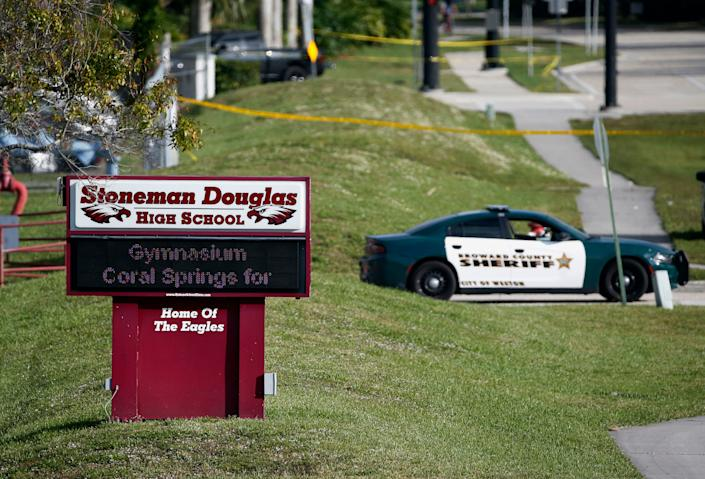 FILE- In this Feb. 15, 2018, file photo, law enforcement officers block off the entrance to Marjory Stoneman Douglas High School in Parkland, Fla., following a deadly shooting at the school. A California man who is on the autism spectrum was sentenced Monday, March 2, 2020, to more than five years in prison for cyberstalking families of Parkland, Florida, school shooting victims. (AP Photo/Wilfredo Lee, File) ORG XMIT: NYHK107