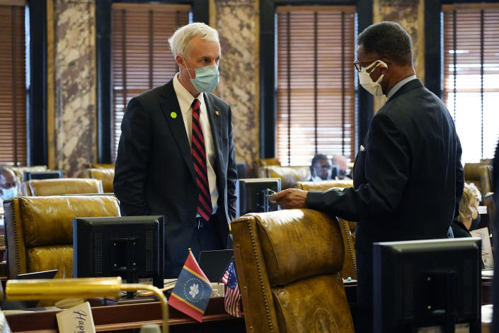 Democratic Sen. David Blount, left, and Sollie Norwood, both of Jackson, confer in the Senate chamber after the body voted 38-7 to pass the required description of the new flag into state law, Wednesday, Jan. 6, 2021 at the Capitol in Jackson, Miss. A small version of the new state flag is displayed along with the American flag on Blount's desk. (AP Photo/Rogelio V. Solis)
