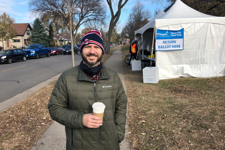 Tim McVean, 38, poses for a photo at a ballot drop-off location in Minneapolis after handing his ballot to election officials on Friday Oct. 30, 2020. McVean said he decided to drop off his ballot in-person after learning of an appeals court ruling Thursday evening that indicated mail-in ballots received after Election Day may not be counted. (AP Photo/Mohamed Ibrahim)