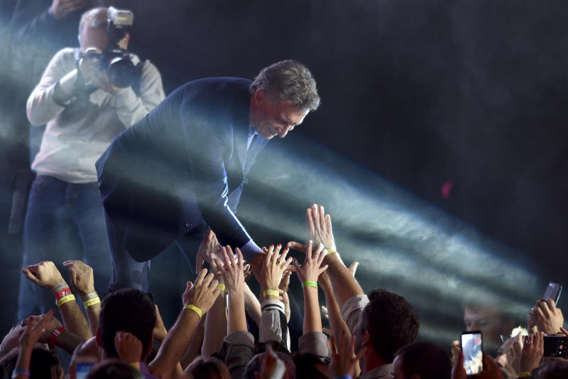 President Mauricio Macri, who was running for reelection, greets supporters after he conceded defeat in Buenos Aires, Argentina, Sunday, Oct. 27, 2019. (AP Photo/Gustavo Garello)