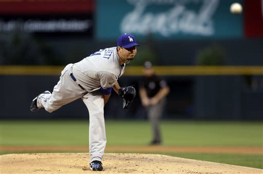 Los Angeles Dodgers starter Josh Beckett follows through on a pitch during the first inning of a baseball game against the Colorado Rockies in Denver on Monday, Aug. 27, 2012. (AP Photo/Joe Mahoney)