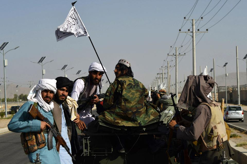 Taliban fighters stand on an armoured vehicle parade along a road to celebrate after the US pulled all its troops out of Afghanistan, in Kandahar on September 1, 2021 following the Talibans military takeover of the country. (Photo by JAVED TANVEER / AFP) (Photo by JAVED TANVEER/AFP via Getty Images)