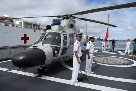 FILE PHOTO: Members of the Chinese People Liberation Army Navy stand by a helicopter on the PLA(N) ship Haikou as it sits docked at Joint Base Pearl Harbor Hickam in Honolulu, Hawaii