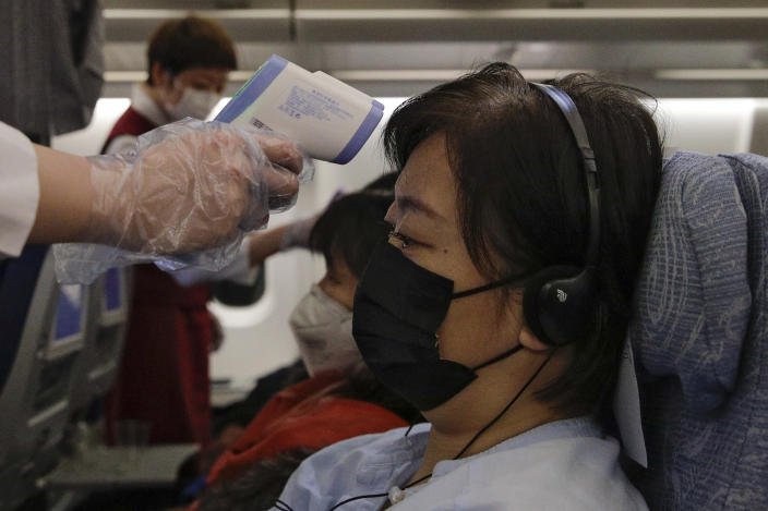 Flight attendants check the temperatures of passengers on a recent Air China flight. (Andy Wong/AP)