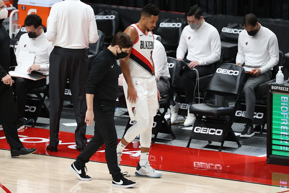PORTLAND, OREGON - JANUARY 16: CJ McCollum #3 of the Portland Trail Blazers has a conversation with a team attendant in the second quarter against the Atlanta Hawks at Moda Center on January 16, 2021 in Portland, Oregon. NOTE TO USER: User expressly acknowledges and agrees that, by downloading and or using this photograph, User is consenting to the terms and conditions of the Getty Images License Agreement. (Photo by Abbie Parr/Getty Images)