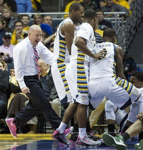Marquette's head coach Buzz Williams, left, runs out to celebrate Davante Gardner's' blocked the shot of Providence's Sidiki Johnson during the first half of an NCAA college basketball game Saturday, Jan. 26, 2013, in Milwaukee. (AP Photo/Tom Lynn)
