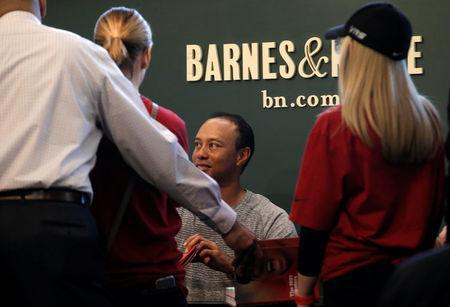 "Golfer Tiger Woods signs copies of his new book ""The 1997 Masters: My Story"" at a book signing event at a Barnes & Noble store in New York City, New York, U.S., March 20, 2017. REUTERS/Mike Segar"