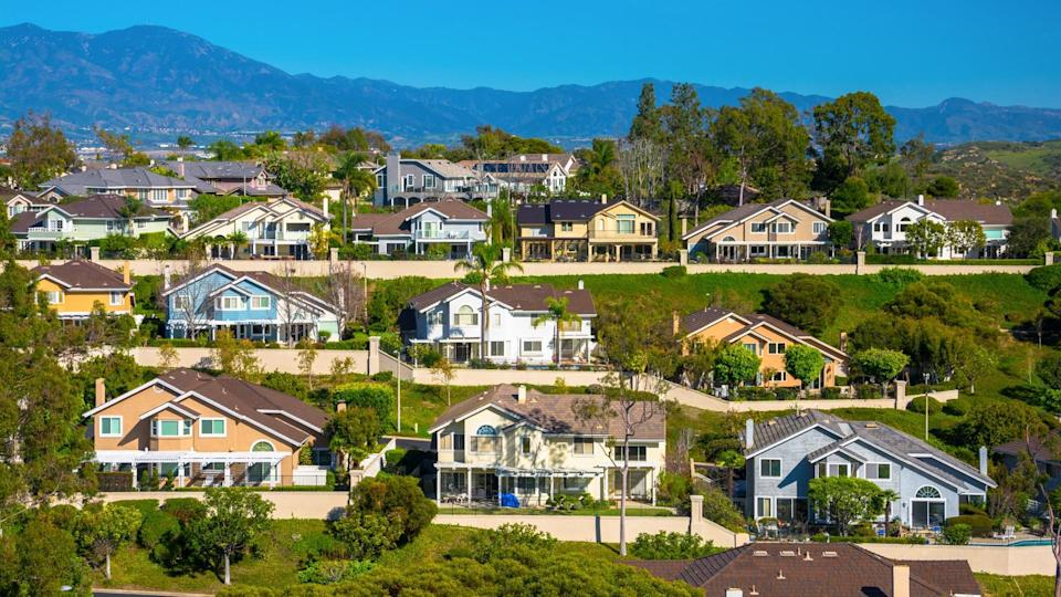 A hillside with many houses in Irvine in southern Orange County, California, with mountains in the background.