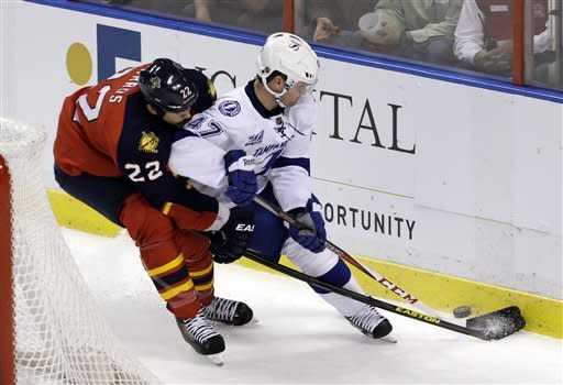 Florida Panthers' George Parros (22) checks Tampa Bay Lightning's Marc-Andre Bergeron (47) in the second period of an NHL hockey game in Sunrise, Fla., Saturday, Feb. 16, 2013. (AP Photo/Alan Diaz)