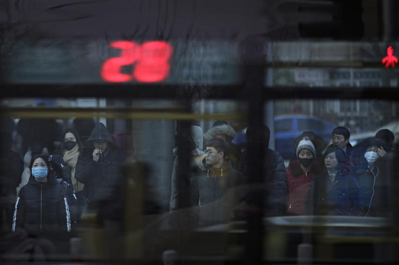 In this Jan. 14, 2019, photo, a bus passes by pedestrians at a traffic intersection in the Central Business District in Beijing. China's slowing economy is squeezing the urban workers and entrepreneurs the ruling Communist Party is counting on to help transform this country from a low-wage factory floor into a prosperous consumer market. (AP Photo/Andy Wong)