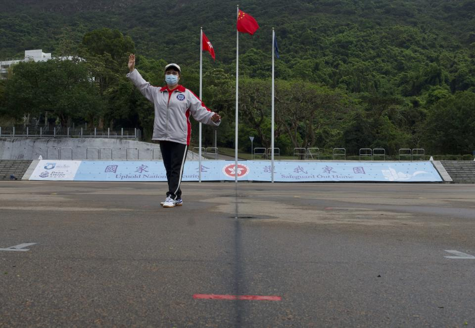 "A woman poses in front of a Chinese national flag on the National Security Education Day at a police school in Hong Kong Thursday, April 15, 2021. Beijing's top official in Hong Kong on Thursday warned foreign forces not to interfere with the ""bottom line"" of national security in Hong Kong, threatening retaliation even amid ongoing tensions between China and Western powers. (AP Photo/Vincent Yu)"