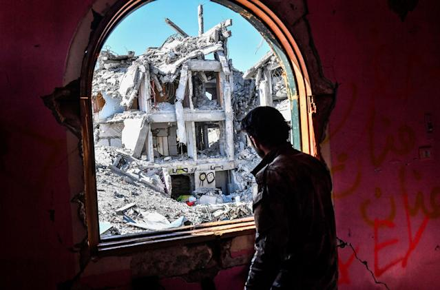 <p>A member of the Syrian Democratic Forces (SDF), backed by US special forces, looks out from a building at the frontline in Raqa on Oct. 16, 2017 in the Islamic State (IS) group jihadist' crumbling stronghold. (Photo: Bulent Kilic/AFP/Getty Images) </p>