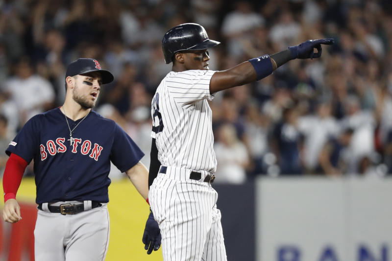 Boston Red Sox second baseman Marco Hernandez, left, watches as New York Yankees' Cameron Maybin gestures toward the Yankees' dugout after hitting a two-run double during the third inning in the second baseball game of a doubleheader Saturday, Aug. 3, 2019, in New York. (AP Photo/Kathy Willens)