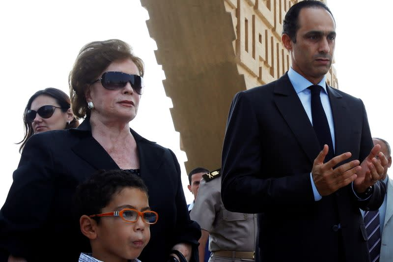 FILE PHOTO: Politician Gamal Mubarak prays with Jehan al-Sadat, the widow of late former President Anwar al-Sadat, at his tomb during his 29th death anniversary in Cairo