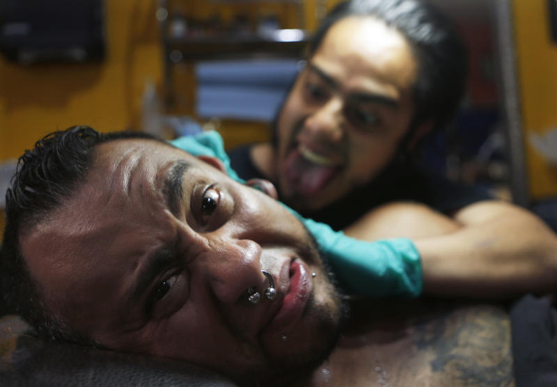 In this April 18, 2019 photo, tattoo artist Lalo Calva inks a tattoo on client Adrian Alonso Rodriguez, a journalist, announcer and dubbing artist, at the Corona Tattoo parlor in Mexico City. Not only inks and techniques have changed in Mexico over the years, but tattoos themselves have evolved from stigmatized symbols of gangs, violence and poverty to an art form. (AP Photo/Marco Ugarte)