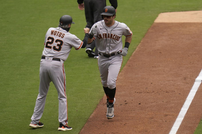 San Francisco Giants' Mike Tauchman, right, is greeted by third base coach Ron Wotus (23) after hitting a three-run home run during the third inning of a baseball game against the San Diego Padres, Sunday, May 2, 2021, in San Diego. (AP Photo/Gregory Bull)