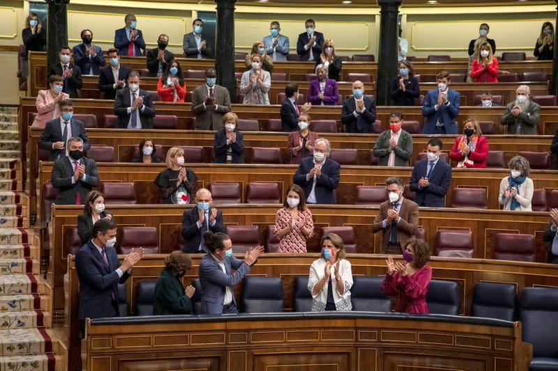 Spanish Prime Minister Pedro Sanchez and deputies applaud during a no confidence motion at Parliament in Madrid